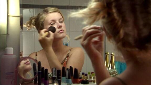 Ein Mädchen steht vor dem spiegel und schminkt sich