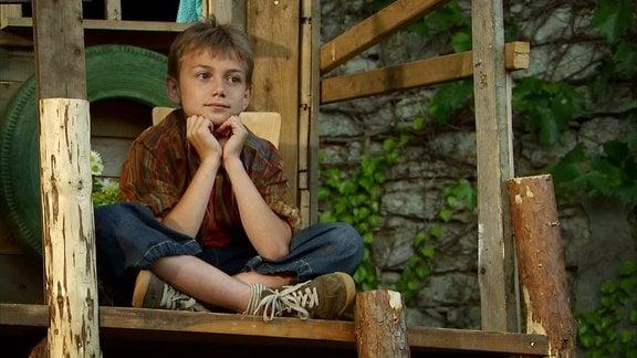 Eine Junge sitzt in seinem Baumhaus