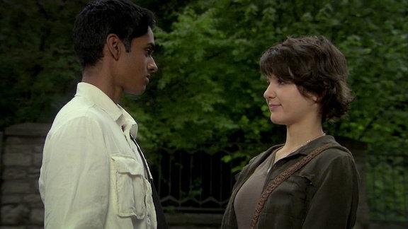 Ein Junge und ein Mädchen stehen in einem Garten