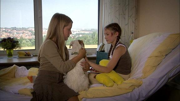 Ein Mädchen im Krankenhaus hat Besuch von einer Freundin mit ihrem Hund