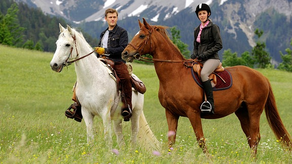 Jovana auf einem fuchsfarbenen Pferd, neben ihr sitzt ihr Ex-Freund auf einem weißen Pferd.