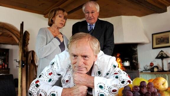 Steffen stützt sich mit zwei Fäusten auf einem Tisch ab. Hinter ihm sehen Maria und ihr Kollege Dr. Franke