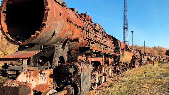 Eine alte rostige Lokomotive steht auf einem Gleis im Freien.