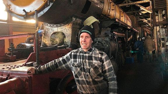 Ein Mann mit Mütze und Holzfällerhemd stützt sich in einer Werkhalle an einer alte Lokomotive ab.