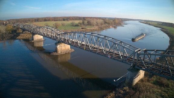 Bahnbrücke über Fluss - ein Frachter nähert sich.