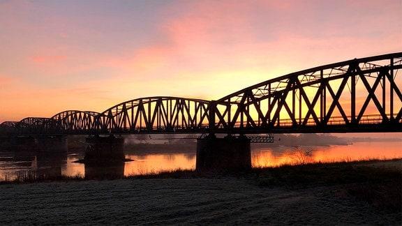 Bahnbrücke über Fluß bei Sonnenuntergang.