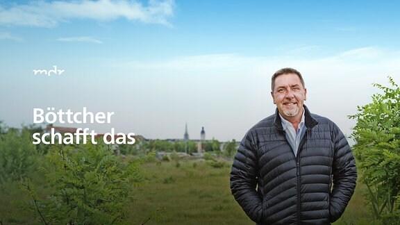 """Der Moderator """"Böttcher"""" steht in Leipzig auf einer grünen Brachfläche."""