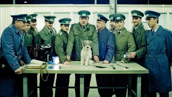 Harald Schäfer (Charly Hübner), Ulrich Rotermund (Milan Peschel), Michael Krüger (Robert Gallinowski), Jens Rambold (Frederick Lau) und andere Grenzsoldaten begutachten den Hund, der kurz zuvor unerlaubt die Grenze überquert hat.