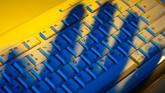 Computer -Tastatur und der Schatten einer Hand