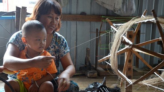 Die Lotosweberin Daw Chaw mit ihrem Neffen an der Spindel.