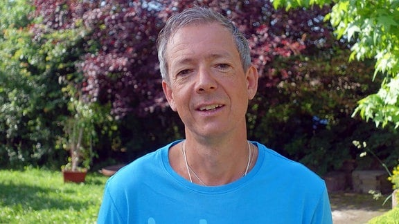 Dr. Ronald Lindner steht in einem Garten.