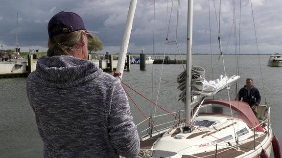 Ein Mann steht auf einem Steg, ein anderer steht am Steuer eines Bootes