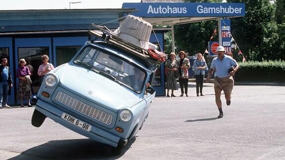 """Trabi """"Schorsch"""" fährt auf zwei Rädern. Udo (Wolfgang Stumph) rennt fassungslos hinterher."""