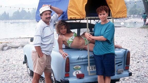"Udo Struutz (Wolfgang Stumph), Jaqueline Struutz (Claudia Schmutzler, Mitte), Rita Struutz (Marie Gruber), Trabi ""Schorsch""."