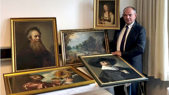 Mann zeigt Gemälde
