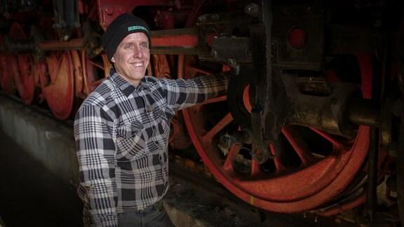 Ein Mann steht or einer alten Lok und lächelt