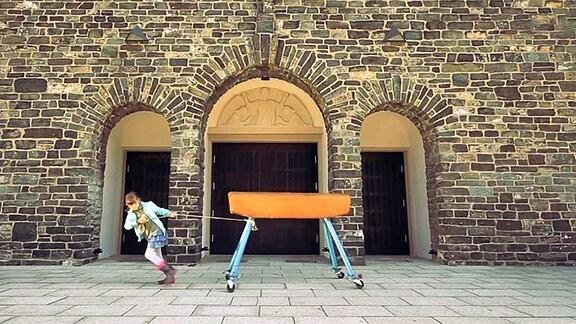 Ein junges Mädchen zieht das Turngerät Pferd hinter sich her.