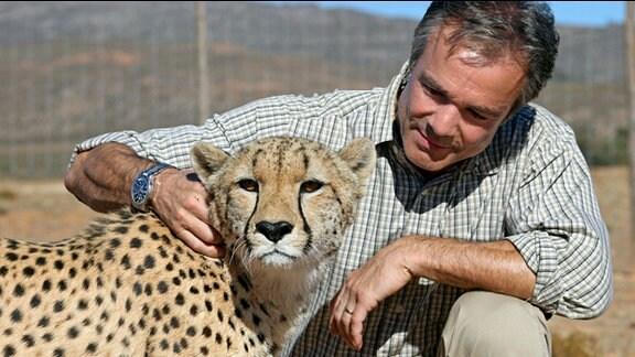 Ein Mann mit einem Gepard.