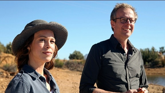 Eine Frau steht neben einem Mann im Feld und schaut in die Ferne.