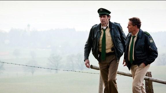 """Hubert (Christian Tramitz, r.) und Staller (Helmfried von Lüttichau, M.) suchen Bauer Weidinger auf dem Feld, da sie diesen wegen """"Beihilfe zum Mord"""" festnehmen wollen."""