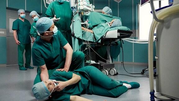 Dr. Kathrin Globisch (Andrea Kathrin Loewig, liegend) bricht während einer Operation plötzlich zusammen. Dr. Roland Heilmann (Thomas Rühmann, stehend, 3.v.re.) bittet Dr. Philipp Brentano (Thomas Koch, kniend), sich um Kathrin zu kümmern und ihn während der weiteren OP auf dem Laufenden zu halten.
