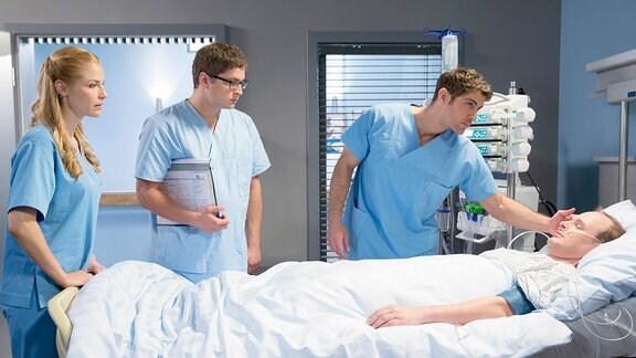 Drei junge Ärzte sind zu einer Visite bei einem männlichen Patienten mittleren Alters, der in einem Krankenbett liegt.