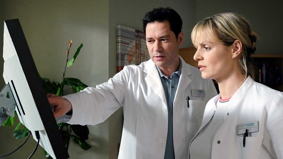 Dr. Philipp Brentano bittet Dr. Lea Peters um Hilfe bei einem Patienten.