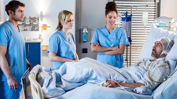Dr. Lea Peters, die Tarik operiert hat, macht ihrem Patienten Mut. Noch haben die Ärzte keine Lösung gefunden, doch sie werden dranblieben und alles tun! V.l.n.r. Dr. Niklas Ahrend (Roy Peter Link), Dr. Lea Peters (Anja Nejarri), Vivienne Kling (Jane Chirwa), Tarik Demir (Erdal Yildiz).