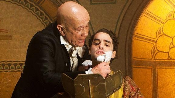 Der Barbier (Christian Grashof) bei der täglichen Rasur des Prinzen Marius (Max Befort)