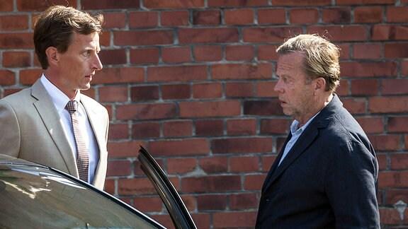 Zwei Männer stehen sich gegenüber, einer von ihnen asteht an einem Auto.