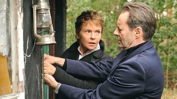 Eine Frau und ein Mann höheren mittleren Alters stehen an einer Hütte im Wald. Er versucht diese zu öffnen.
