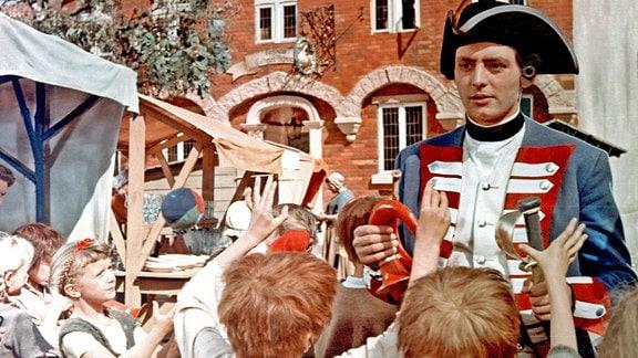 Der Soldat (Rolf Ludwig) geht auf den Markt und kauft den Kindern mit seinem Gold Süßigkeiten und Spielzeug