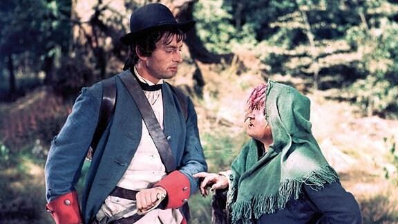 Vom König um seinen Sold betrogen zieht der Soldat (Rolf Ludwig) in die Welt hinaus und begegnet im Wald einer Hexe (Bella Waldritter)