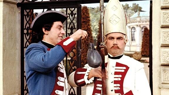 Vor dem Kupferschloss des Königs versucht der Soldat (Rolf Ludwig) den Wachsoldaten mit Gold zu bestechen