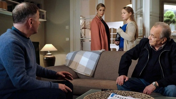 Sarah Marquardt und Sarah verlassen das Wochnzimmer. Prof. Simoni und Roland Heilmanns sitzen auf dem Sofa.