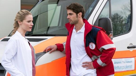 Zwei Ärzte stehen vor einem Krankenwagen. Während der junge Mann die junge Ärztin anschaut, blickt sie nachdenklich an ihm vorbei.