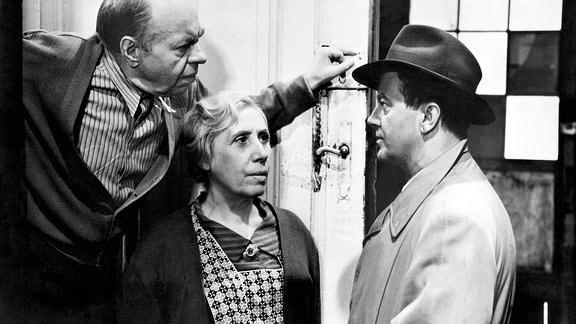 Mörder Erwin Retzmann (Gert Gütschow) gibt sich bei den Nachbarn (Agnes Kraus, Heinz Scholz) seines Opfers als Kommissar aus