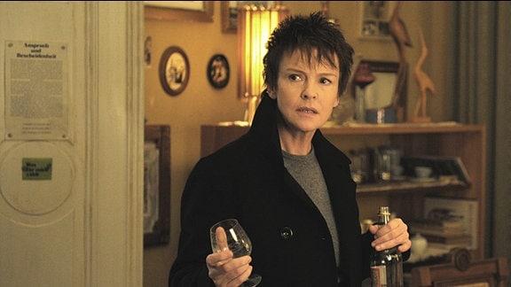 Eine Frau mit kurzen, rötlichen Haaren hält ein Weinbrandglas in der Hand.