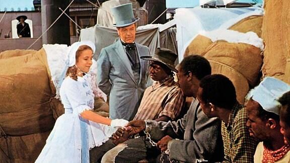 Die kleine Eva Saint Claire (Gertrud Mittermayr, l.) fühlt sich sehr hingezogen zu Onkel Tom (John Kitzmiller, 3.v.r.), der zusammen mit anderen verkauften Sklaven auf einem Mississippi-Dampfer einem ungewissen Schicksal entgegenfährt.