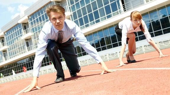 Zwei junge Menschen setzen zum Sprint an, um ihre Karriere zu starten.