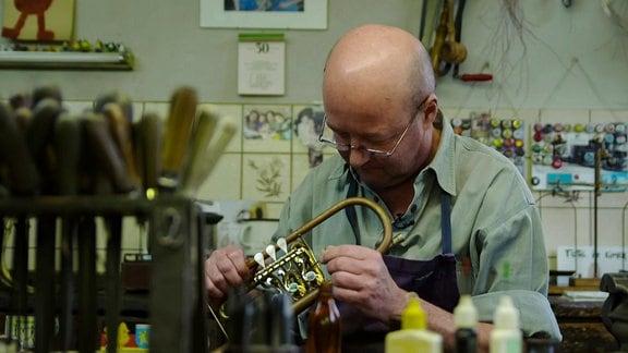 Ein Mann untersucht eine Trompete
