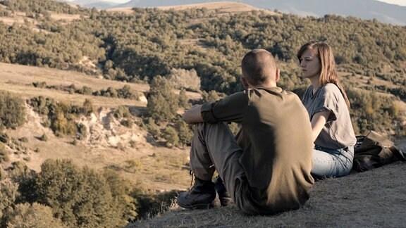 Zwei Menschen sitzen am einem Wegrand und unterhalten sich. Im Hintergrund bewaldete, sanft geschwungene Täler und Hügel.