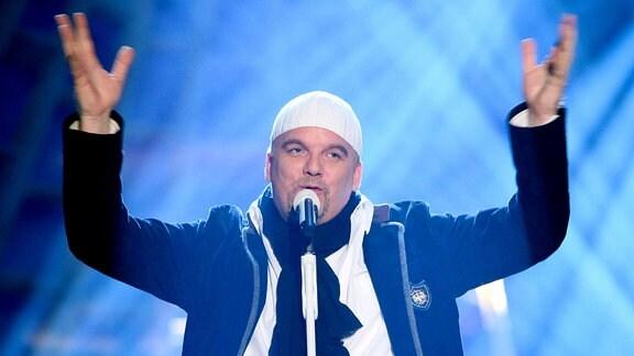 DJ Ötzi steht auf einer Bühne und hebt beim Singen die Arme.