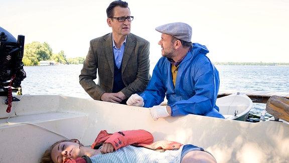 Zwei Männer hocken an einem Boot mit einer Leiche darin.