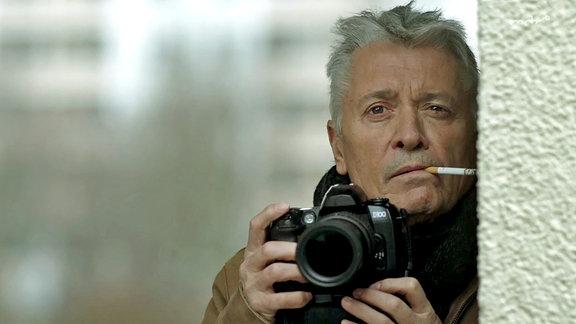 Ein Mann (Henry Hübchen) lauert mit einer Kamera im Anschlag.