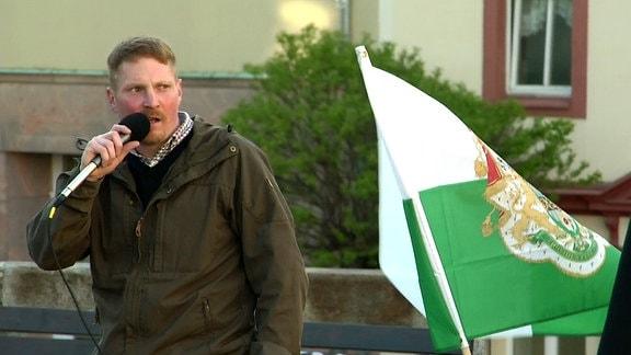 Ein Mann spricht auf einer Kundgebung