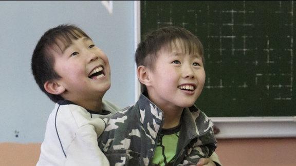 Aljoscha und sein Freund raufen gemeinsam im Klassenzimmer