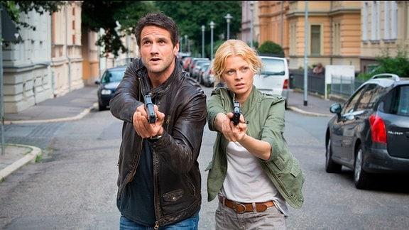 Die Kommissare Kristina Katzer (Isabell Gerschke, r.) und Lukas Hundt (Oliver Franck, l.) mit gezogener Pistole auf Verbrecherjagd in Weimar.