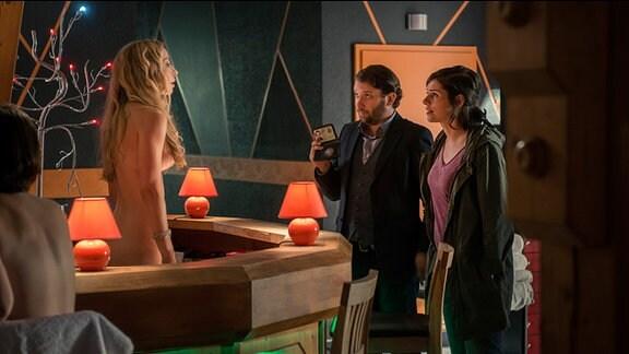 "Lessing (Christian Ulmen) und Kira Dorn (Nora Tschirner) befragen Peggy Schuhschnabel (Michelle Monballijn,li.) im ""FKK Paradies""."
