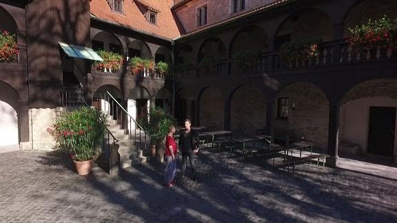 Eine Frau und ein Mann stehen im Hof eines Klosters in Erfurt und unterhalten sich.